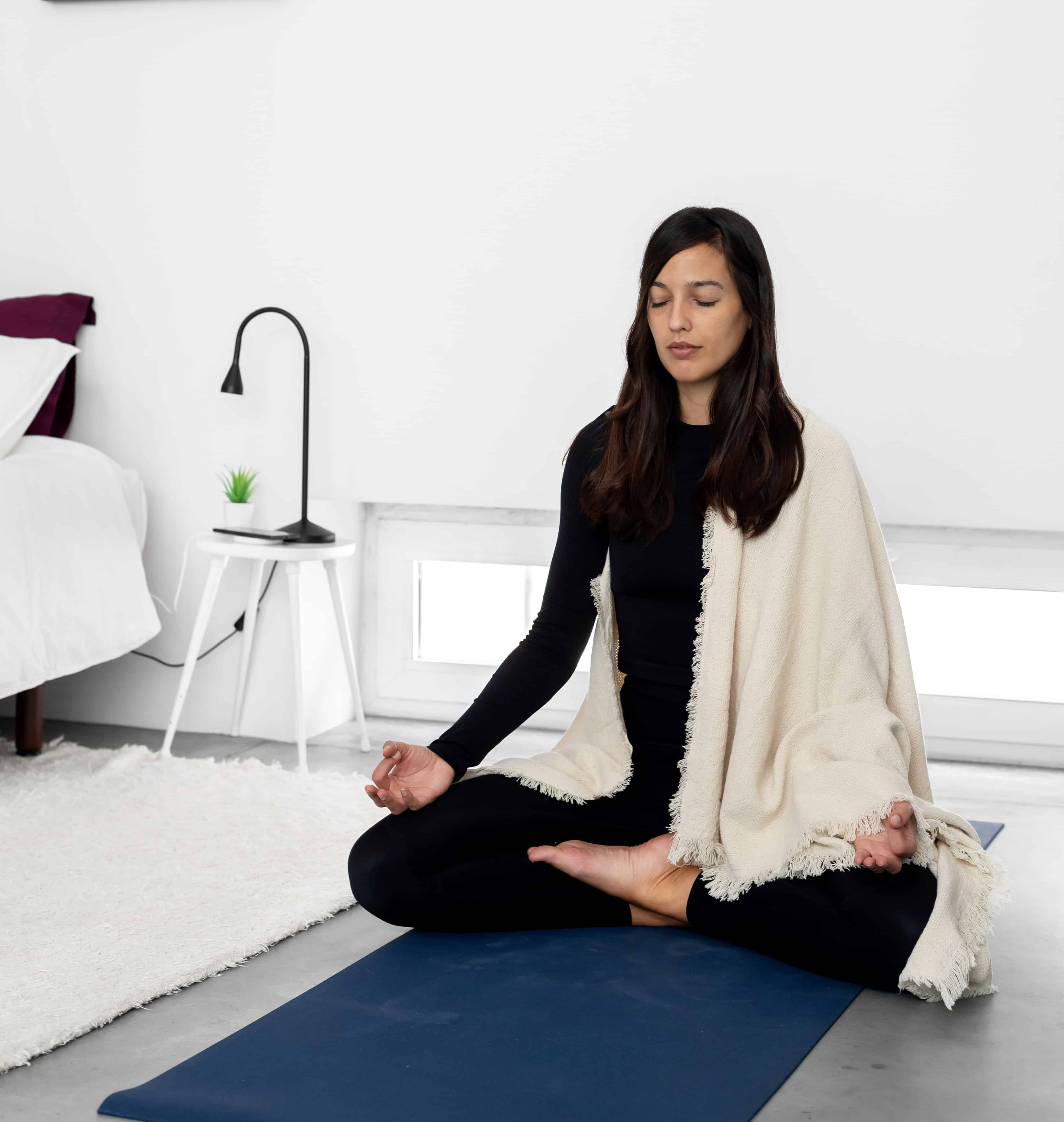 Tranquil young woman in sportswear and shawl practicing meditation in lotus pose in minimalist style room at home