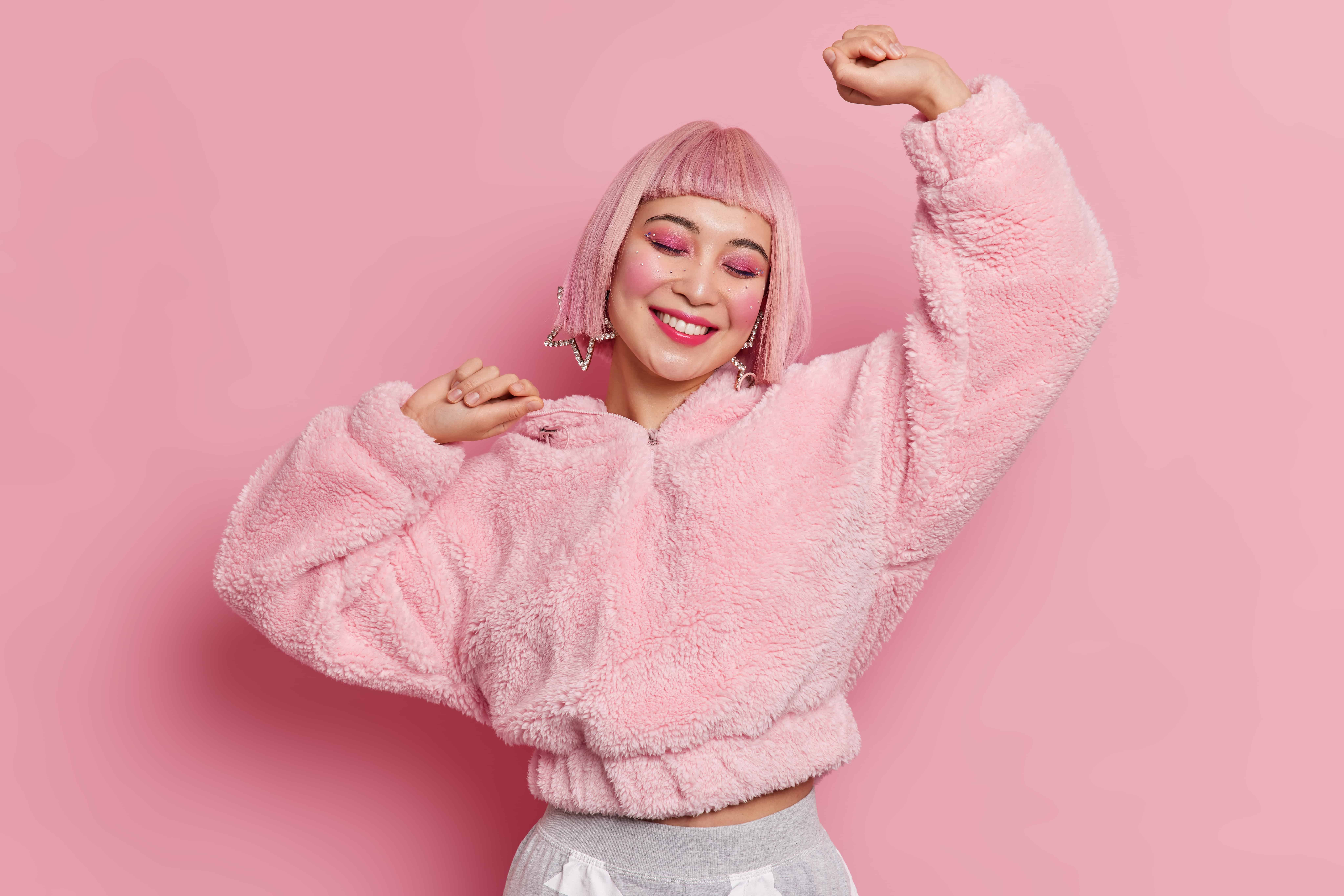 Studio shot of cheerful young pretty Asian woman wears pink wig bright makeup raises arms feels upbeat dances carefree celebrates something dressed in fur coat isolated over rosy background.