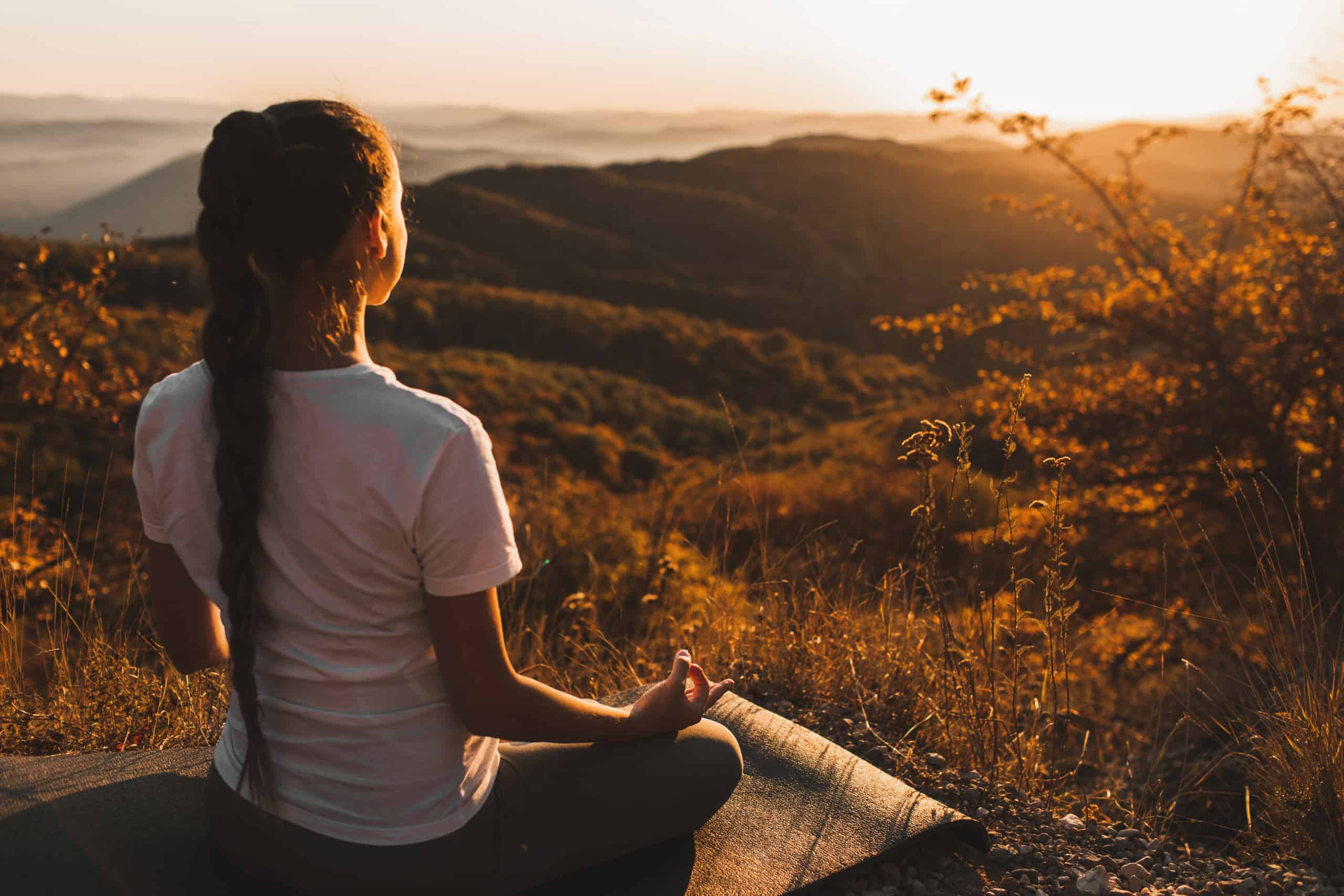 Woman meditating alone on hill with amazing autumn mountain view
