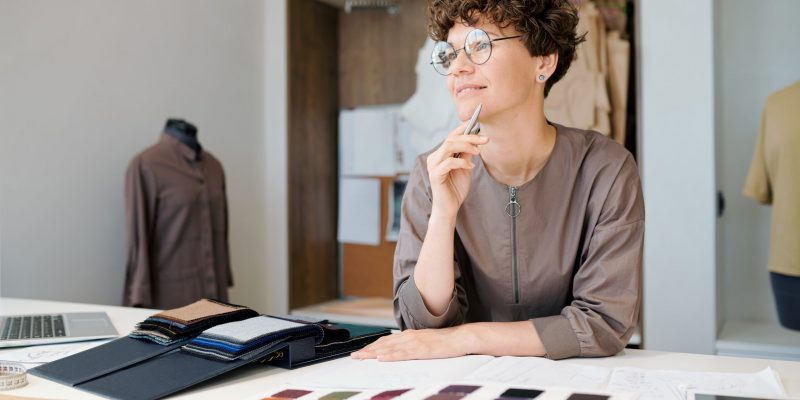 Happy young female creative designer thinking of ideas while working over new collection by workplace