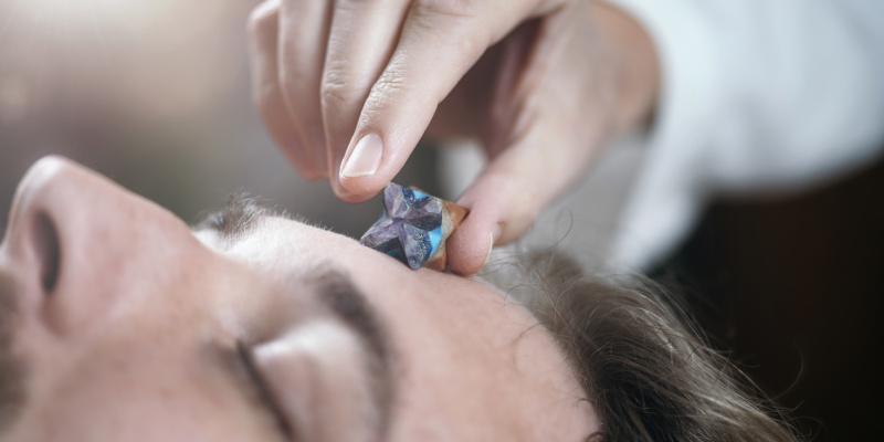 Healing crystal. Young man with Merkaba crystal placed on his forehead on third eye's area.