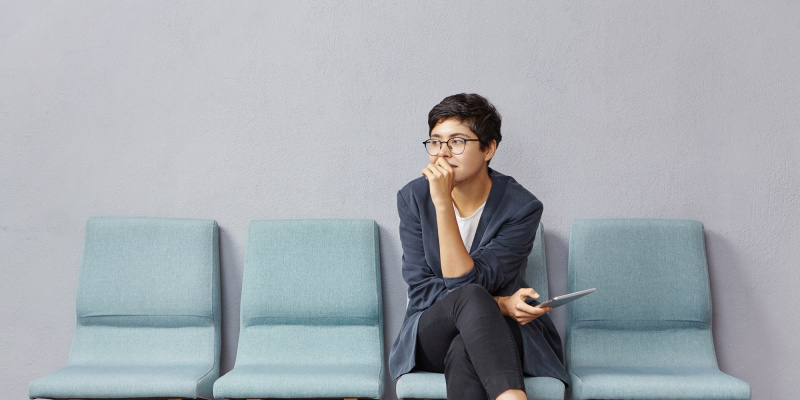Picture of attractive fashionable young female designer wearing trendy clothes and eyeglasses sittin