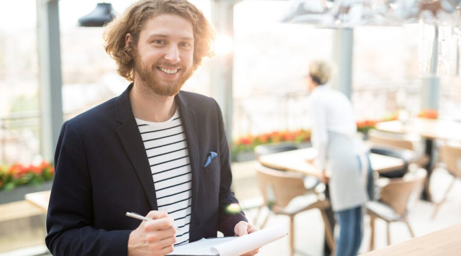 Happy businessman with document making notes about new restaurant